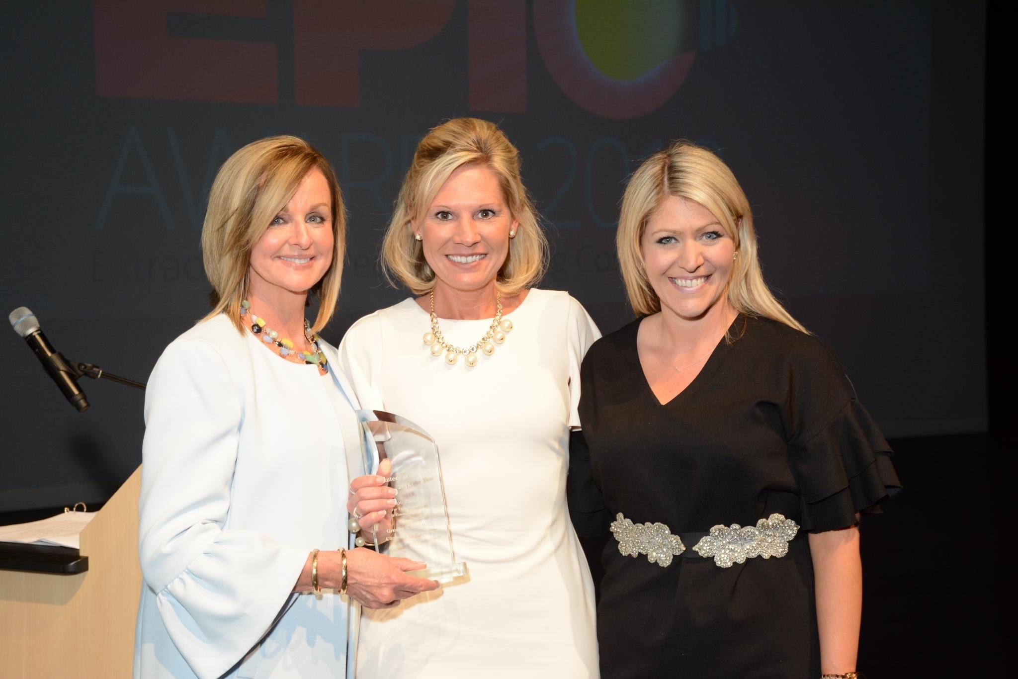 Three Women Smile While Holding an Award