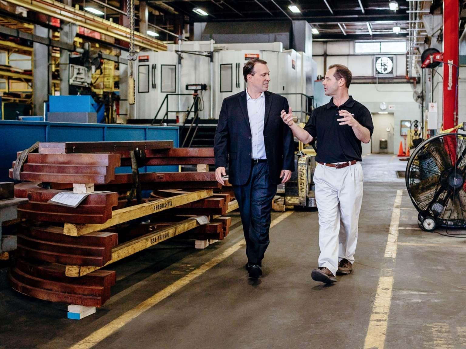 Two Men Walking In Warehouse
