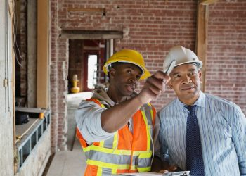 two construction workers pointing