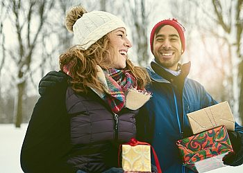 Couple in Winter Clothes Carrying Presents