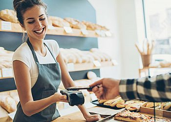 Woman Behind Bakery Counter Cashing Out Customer
