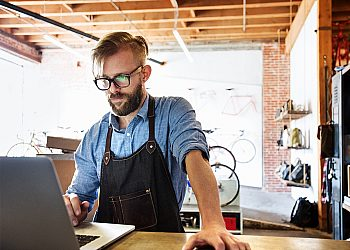 man-with-apron-on-laptop