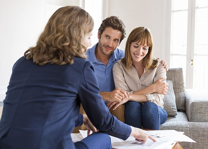 Couple Smiling While Meeting With Meeting with Financial Advisor