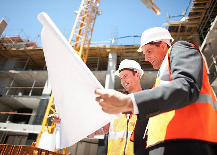 Two Construction Workers Holding Blueprint at Construction Site