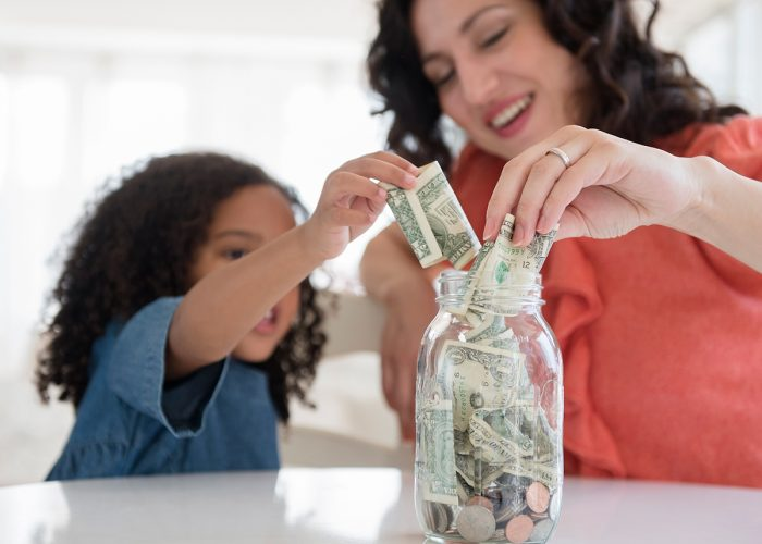 mom and daughter putting money in jar