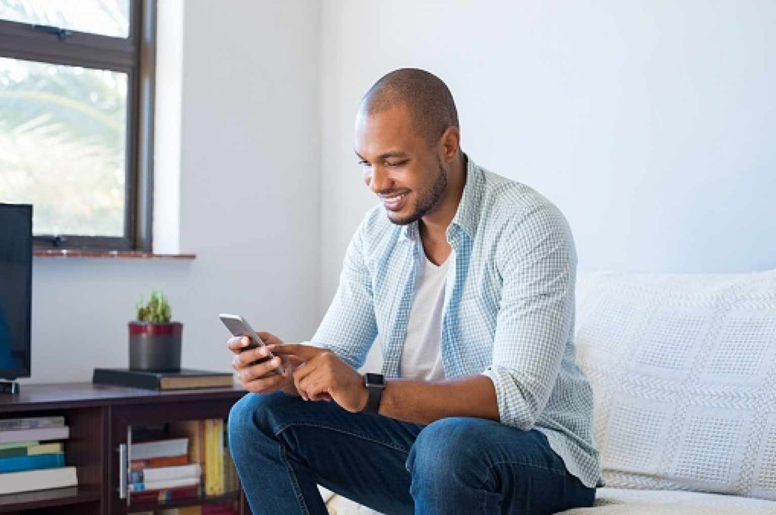 Man Smiling While Looking at Phone