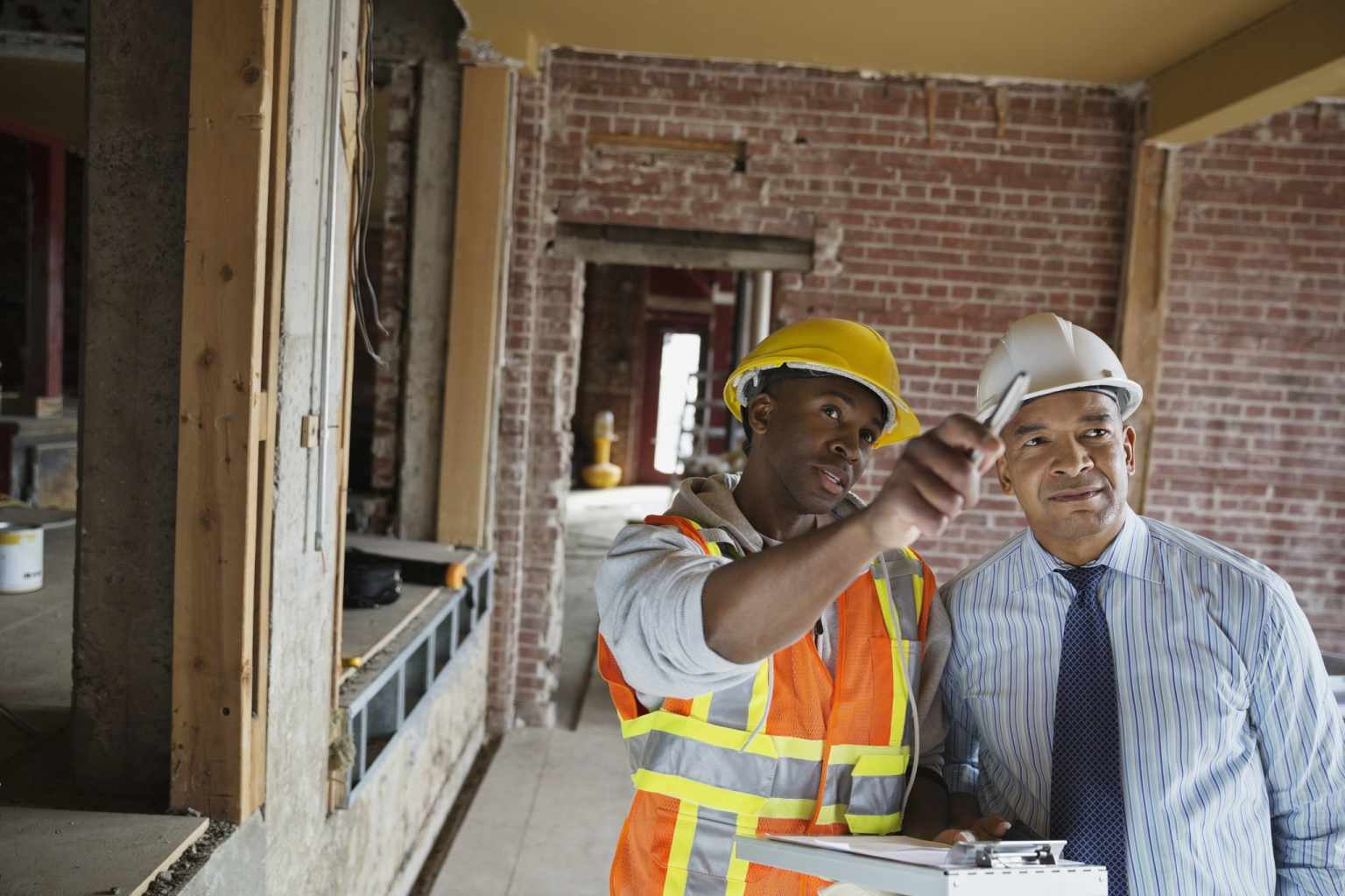 Two Men Speaking at Construction Site