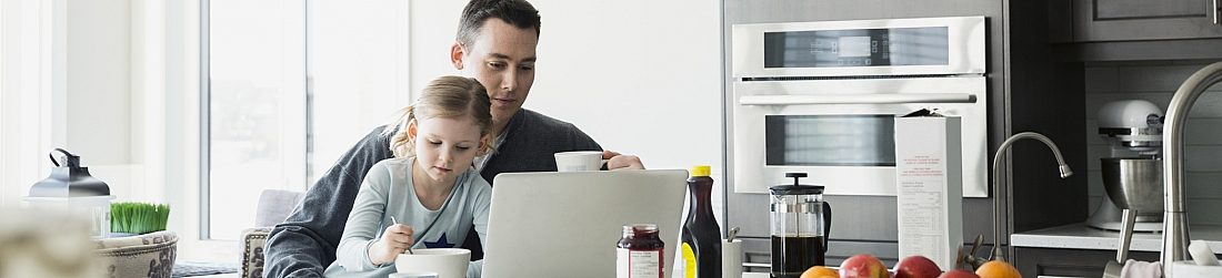 Father Drinking Coffee While Looking at Computer With Daughter